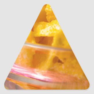 Defocused and blurred macro view of yellow flakes triangle sticker