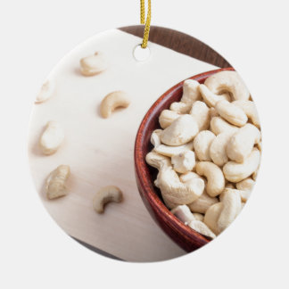 Delicious and healthy raw cashew nuts round ceramic ornament