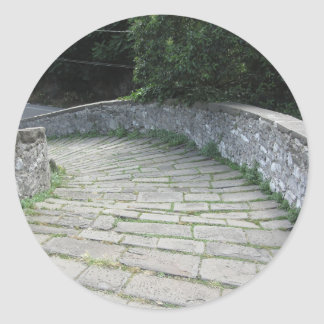 Descent stone walkway of medieval bridge round sticker