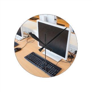 Desktop computer in computer class on school round clock