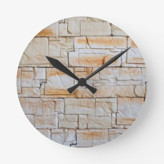 Detail of a decorative wall of limestone tiles wall clock