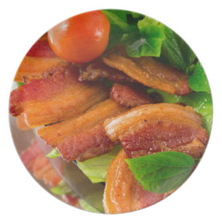 Detail of a plate of fried bacon and cherry tomato