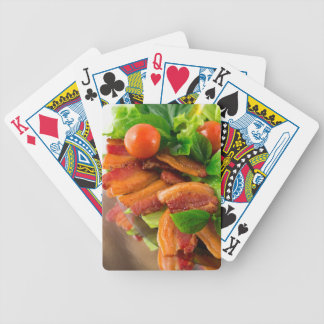 Detail of a plate of fried bacon and cherry tomato bicycle playing cards
