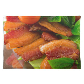 Detail of a plate of fried bacon and cherry tomato placemat
