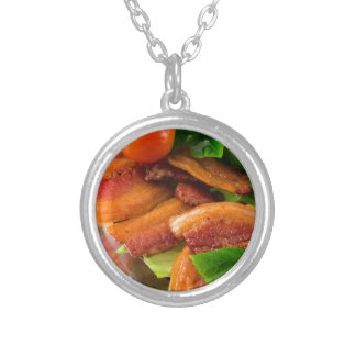 Detail of a plate of fried bacon and cherry tomato silver plated necklace
