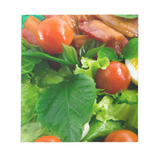 Detail of a plate with cherry tomatoes, herbs notepad