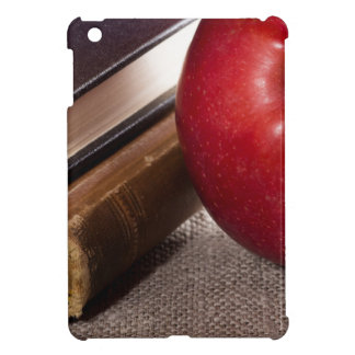 Detail of old books in hardcover and red apple cover for the iPad mini