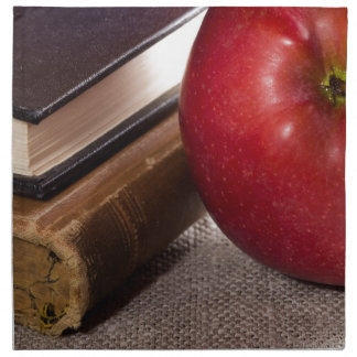 Detail of old books in hardcover and red apple napkin