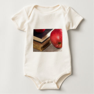Detailed close-up view of the red apples and old baby bodysuit