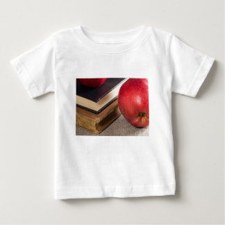 Detailed close-up view of the red apples and old baby T-Shirt