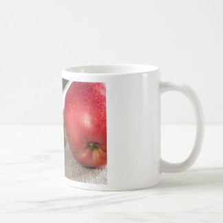 Detailed close-up view of the red apples and old coffee mug
