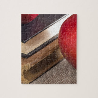 Detailed close-up view of the red apples and old jigsaw puzzle