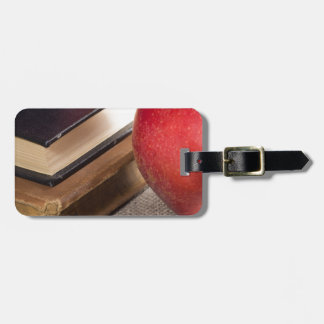 Detailed close-up view of the red apples and old luggage tag