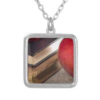 Detailed close-up view of the red apples and old silver plated necklace