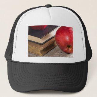 Detailed close-up view of the red apples and old trucker hat