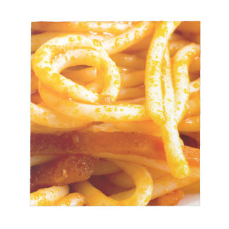 Detailed macro view on cooked spaghetti on a plate notepad