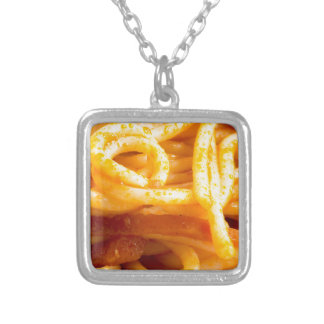 Detailed macro view on cooked spaghetti on a plate silver plated necklace