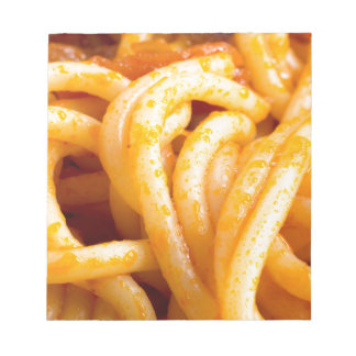 Detailed macro view on cooked spaghetti with sauce notepad