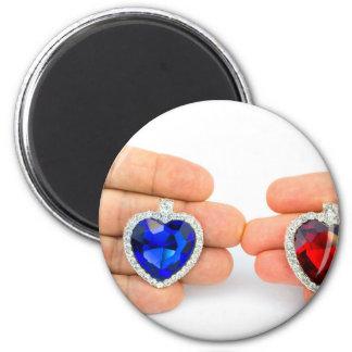 Deux coeurs de bijoux en main de l'homme et de magnet rond 8 cm
