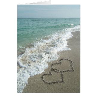 Deux coeurs de sable sur la plage, océan carte de vœux