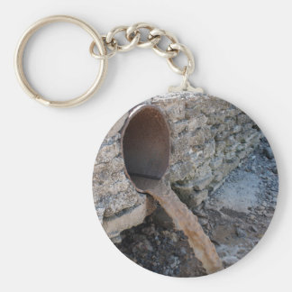 Dirty water flows from a brown rusty sewer pipes keychain