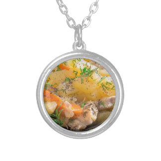 Dish of stewed potatoes with chicken and spices silver plated necklace