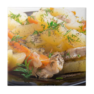 Dish of stewed potatoes with chicken and spices tiles