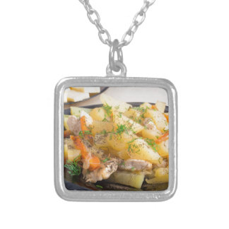 Dish of stewed potatoes with meat and spices silver plated necklace