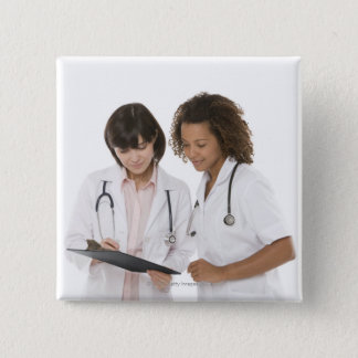 Doctors looking at clipboard 2 inch square button