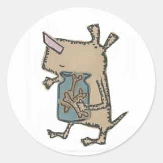 Dog holding his bones round sticker