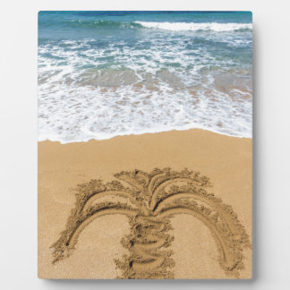 Drawing of palm tree on sandy beach plaque