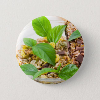 Dry mix of muesli and cereal in a bowl of glass 2 inch round button