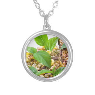 Dry mix of muesli and cereal in a bowl of glass silver plated necklace