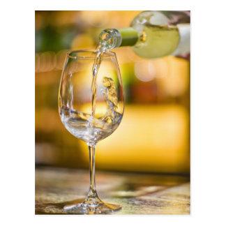 Du vin blanc est versé de la bouteille dans le carte postale