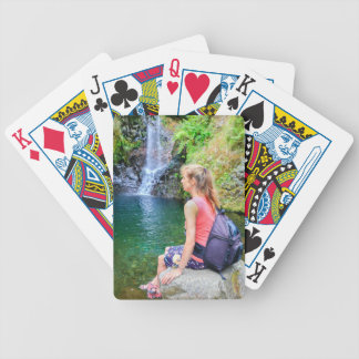 Dutch woman sitting on rock near waterfall bicycle playing cards