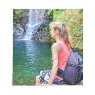Dutch woman sitting on rock near waterfall notepad