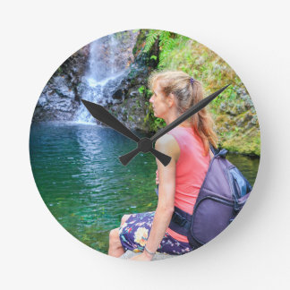 Dutch woman sitting on rock near waterfall round clock