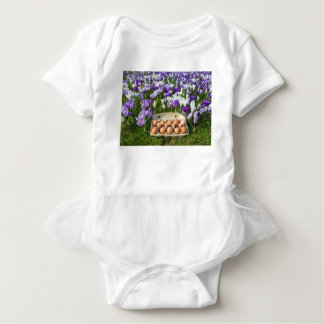 Egg box with chicken eggs in crocuses baby bodysuit