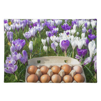 Egg box with chicken eggs in crocuses placemat