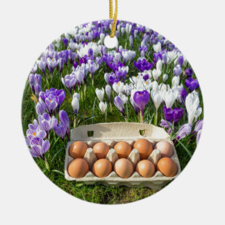 Egg box with chicken eggs in crocuses round ceramic ornament