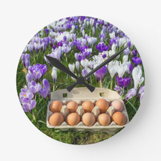 Egg box with chicken eggs in crocuses round clock