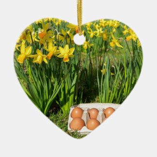 Eggs in box on grass with yellow daffodils ceramic heart ornament