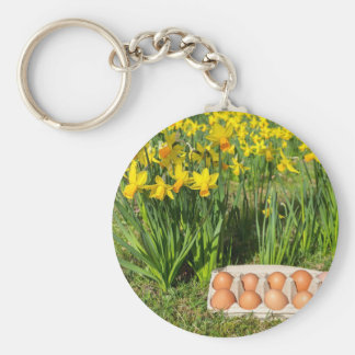 Eggs in box on grass with yellow daffodils keychain