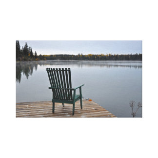 Empty chair on lake deck canvas print