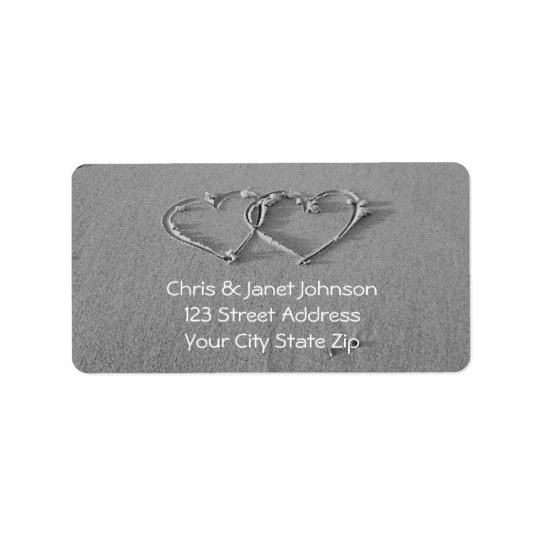 Entwined hearts in beach sand address labels