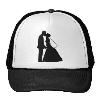 Épouser la silhouette de jeunes mariés de baiser casquettes