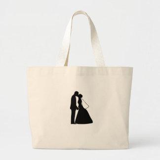 Épouser la silhouette de jeunes mariés de baiser sacs de toile