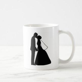 Épouser la silhouette de jeunes mariés de baiser tasse à café