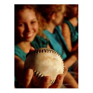 Équipe du base-ball des adolescentes s asseyant da carte postale