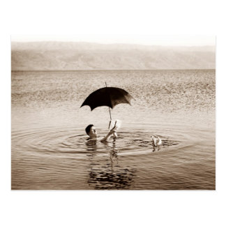 Équipez la lecture sous le parapluie en mer morte carte postale